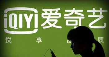 side view of woman's head in front of QIY logo