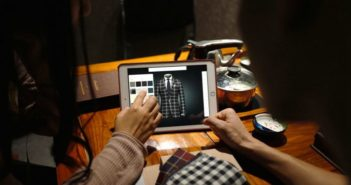 back view of two girls looking at clothes on an ipad