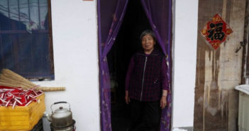 old lady standing in doorway at home in china