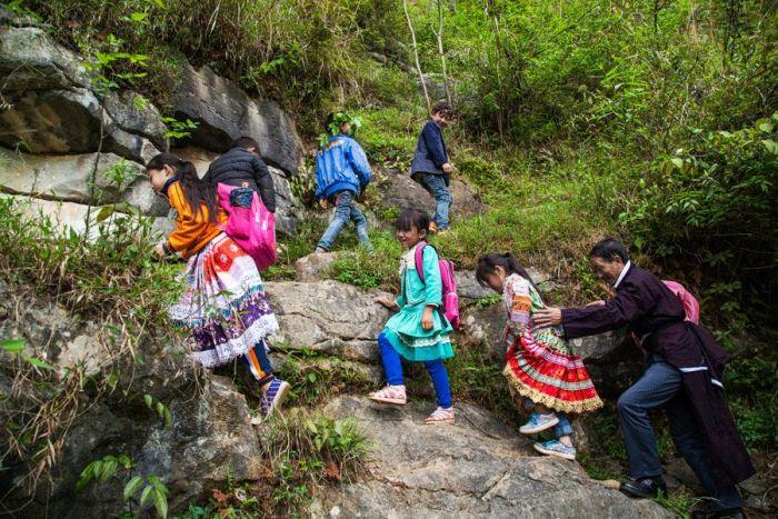 children and teacher climbing mountain roads