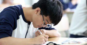 boy sitting at a desk doing school work