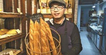 baker holding basket of baguette in china