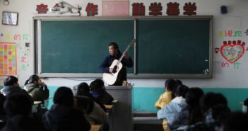 music teacher playing guitar in class in china