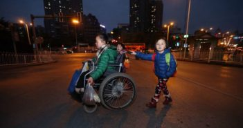 side view of woman in wheelchair crossing road with children in china