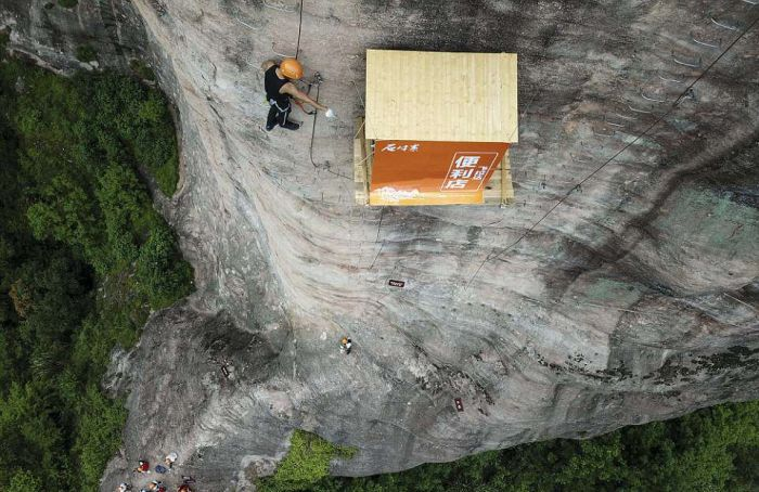 top view of mountain climber and shop on cliff face in china