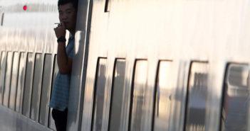 man smoking in doorway of train in china