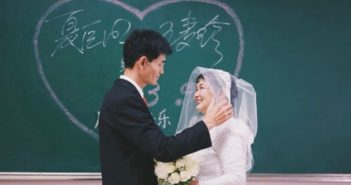 couple in wedding attire standing in front of a blackboard