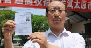 man holding identification paper for picture