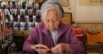front view of old lady sitting at desk making writing brushes in china