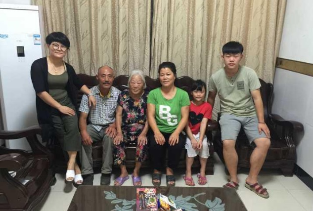 family and old lady sitting on sofa at home