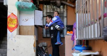 side view of security guard father carrying sick son in china