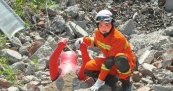 top view of a young rescue worker crouching on rubble after an earthquake in sichuan