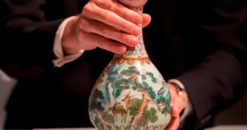auctioneer holding a qing dynasty vase