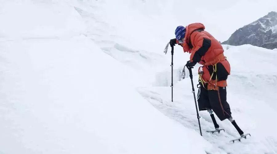 side view of double amputee climbing up snowy mountain