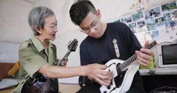 elderly teacher teaching young student to play mandolin