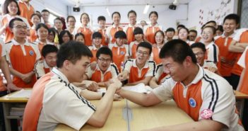 students armwrestling in classroom at high school in china