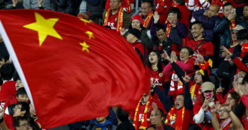 Chinese fans celebrate a goal with the national flag