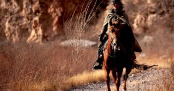 chinese man riding horse in wilderness in russia