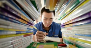 boy studying seen through tunnel of books