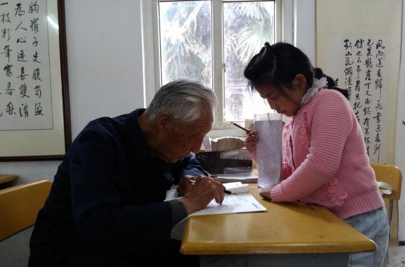 side view of old man giving class to young girl