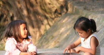 two girls plying outside