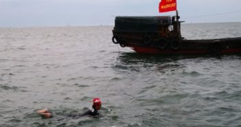 woman swimming past boat in qiongzhou strait