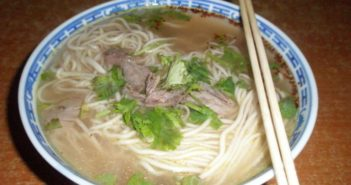 bowl of lanzhou la mian with chopsticks on a table