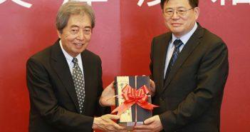 former japanese prime minister Morihiro Hosokawa presenting books to representative from chinese national library