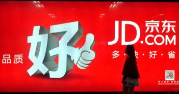 woman walking past JD.com street ad