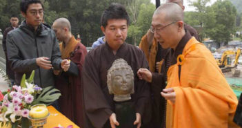 buddhist monks holding buddha head statue at temple in china