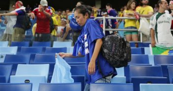 japanese fan with rubbish bag in stands at world cup game