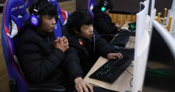 side view of two teens playing computer games in china