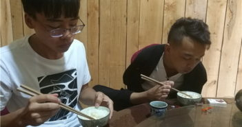 two brothers eating at the table, one with his hands and the other with his feet