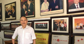man posing for picture in front of photos on wall at home