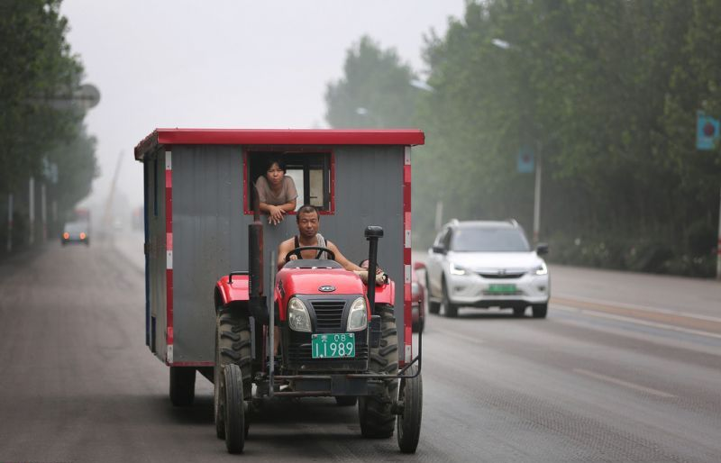 front view of man driving tractor down road in china