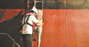 crewman helping woman up side of cargo ship ladder