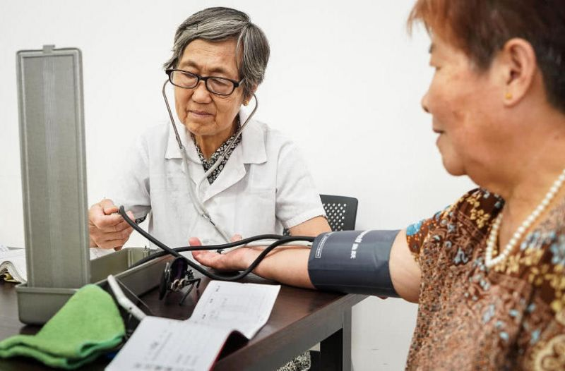 elderly doctor taking patient's blood pressure in china