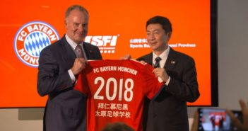 bayern munich and shanxi official holding football shirt and posing for photo on stage