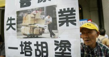 elderly man holding protest sign in hong kong