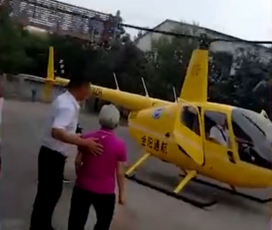 back view of pilot walking elderly woman to helicopter in china