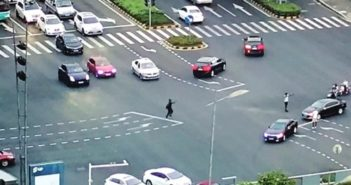 expat in middle of intersection directing traffic in suzhou