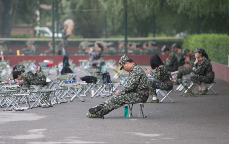students sitting down with mobile phones during military training in china