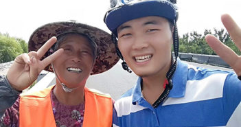 student cyclist posing for photo with sanitation worker