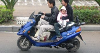 side view of couple with baby on electric scooter