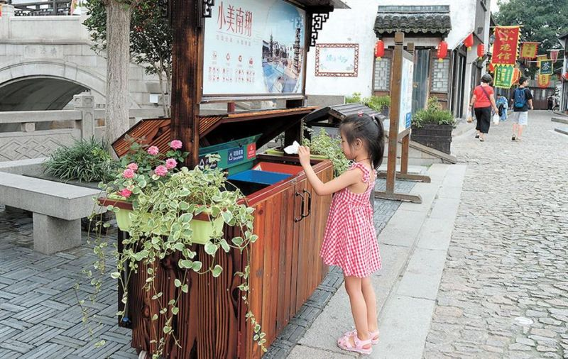 girl putting rubbish in bin in shanghai