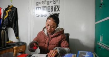 tibet girl behind desk at work at post office on mount everest
