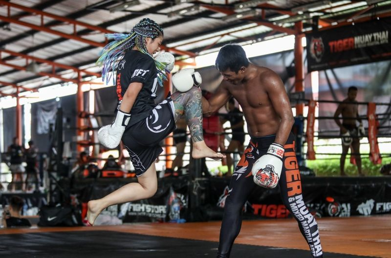 girl practicing muay thai with instructor