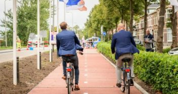 back view of two men on bikes cycling down road made from plastic waste in holland