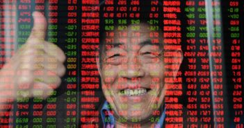 chinese man giving thumbs up behind stock prices