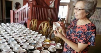 woman showing teaware collection on dining room table